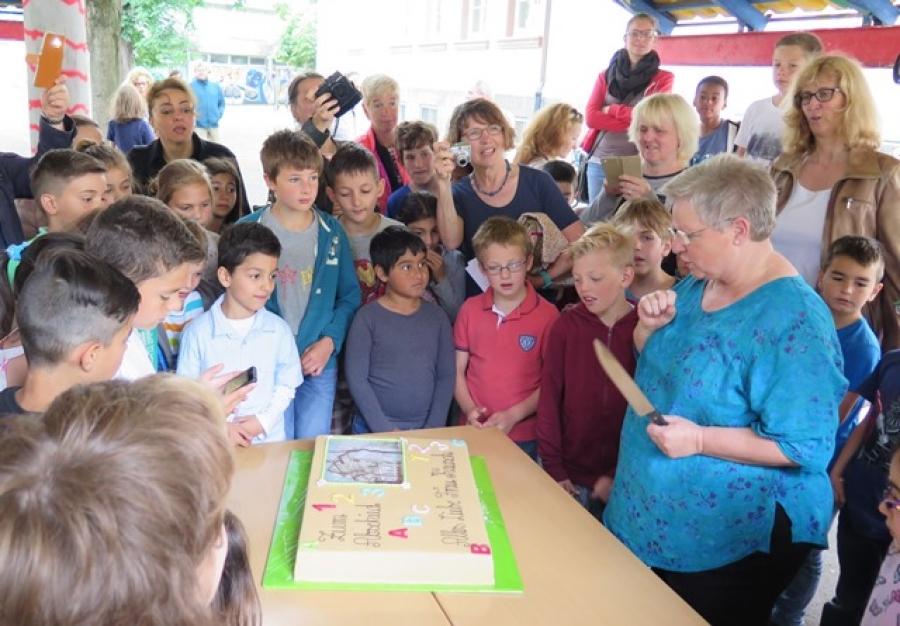 Kinder, Lehrer und Eltern verabschieden sich von der Schulleiterin